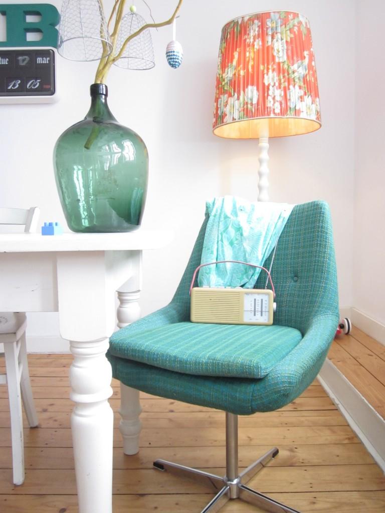 Ein emeraldfarbener Stuhl aus den 60er Jahren steht in meinem Wohnzimmer mit einem Glasballon und einer Flipclockuhr.